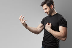 The Oath. A handsome muscular man posing in the act of a oath wearing a black t-shirt and a pair of jeans Royalty Free Stock Image