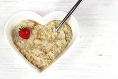 Oatmeal ή κουάκερ προγευμάτων σε ένα διαμορφωμένο καρδιά κύπελλο Αγροτική ΤΣΕ Στοκ εικόνα με δικαίωμα ελεύθερης χρήσης