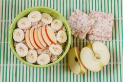 Oatmeal κουάκερ με τη Apple και φέτες μπανανών στο πράσινο κύπελλο Στοκ Φωτογραφία