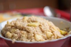 Oatmeal κουάκερ με το μήλο και μπανάνα στη στενή επάνω εστίαση πιάτων ανασκόπηση που θολώνεται Στοκ Φωτογραφίες