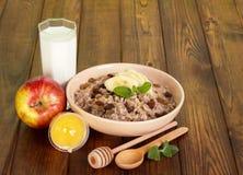 Oatmeal κύπελλων με τις σταφίδες και την μπανάνα, γάλα, μέλι, μήλο Στοκ Εικόνα