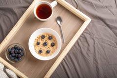 Oatmeal με τα μούρα σε έναν δίσκο στο κρεβάτι με το τσάι, το πρόγευμα πρωινού και τη διάθεση r καλός και θερμός στοκ φωτογραφίες