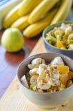 Oatmeal με την μπανάνα, την πορτοκαλιά, πράσινη Apple, τα ξύλα καρυδιάς, τους σπόρους σουσαμιού και Chia Στοκ Φωτογραφίες