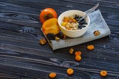 Oatmeal με Persimmon σε έναν μαύρο ξύλινο πίνακα στοκ εικόνες