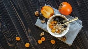 Oatmeal με Persimmon σε έναν μαύρο ξύλινο πίνακα στοκ φωτογραφίες
