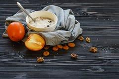 Oatmeal με Persimmon σε έναν μαύρο ξύλινο πίνακα στοκ εικόνες με δικαίωμα ελεύθερης χρήσης