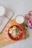 Oatmeal προγευμάτων κουάκερ με τις μπανάνες, τους σπόρους, τα καρύδια και το γάλα Στοκ Εικόνες