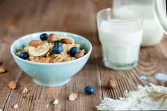 Oatmeal πρόγευμα κουάκερ με τα καρύδια, τα μούρα και το γάλα Στοκ Εικόνες