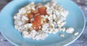 Oatmeal σε ένα πιάτο με τη μαρμελάδα φιλμ μικρού μήκους