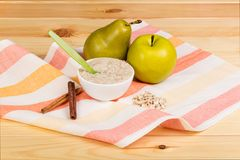 Oatmeal στο κύπελλο με το κουτάλι, το αχλάδι και τη Apple στη ριγωτή πετσέτα στο υπόβαθρο του πίνακα Στοκ Εικόνες