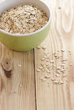 Oatmeal. In a green bowl on a wooden background Stock Photos