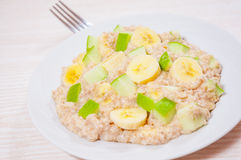 Oatmeal with apple and bananas slices Royalty Free Stock Photos