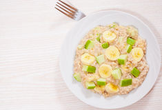 Oatmeal with apple and bananas slices Stock Images