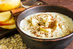 Oatmeal with apple and cinnamon in the bowl. On the wooden rustic background with sliced apple. healthy breakfast Stock Photos
