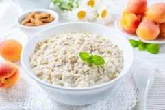 Oatmeal with apricot and nuts in bowl on white wooden table royalty free stock image