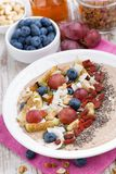 Oatmeal with assorted fruits, nuts and chia, vertical, closeup. Top view stock photos