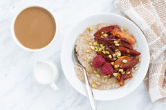Oatmeal with baked fruit and fresh coffee with milk, top view Stock Photography