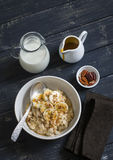Oatmeal with banana, caramel sauce and pecan nuts in a white bowl on a dark wooden surface Royalty Free Stock Image