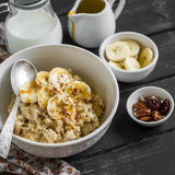 Oatmeal with banana, caramel sauce and pecan nuts in a white bowl on a dark wooden surface. A delicious and healthy Breakfast stock image