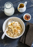 Oatmeal with banana, caramel sauce and pecan nuts in a white bowl on a dark wooden surface Stock Photo