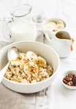 Oatmeal with banana, caramel sauce and pecan nuts in a white bowl Royalty Free Stock Photography
