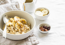 Oatmeal with banana, caramel sauce and pecans in a white bowl on a light surface Royalty Free Stock Images