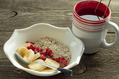 Oatmeal, banana and frozen strawberries in white bowl and cup of Stock Photo