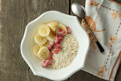 Oatmeal, banana and frozen strawberries in white bowl Royalty Free Stock Photography