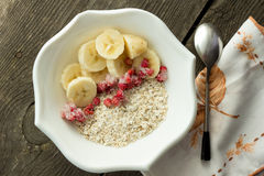 Oatmeal, banana and frozen strawberries in white bowl Stock Photo