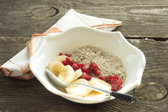 Oatmeal, banana and frozen strawberries in white bowl Stock Images