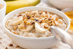 Oatmeal with banana, honey and walnuts in bowl for breakfast Royalty Free Stock Photography