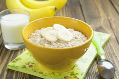 Oatmeal with bananas. Porridge with bananas in a yellow bowl and a glass of milk on the table Royalty Free Stock Images