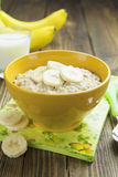 Oatmeal with bananas. Porridge with bananas in a yellow bowl and a glass of milk on the table Royalty Free Stock Photos