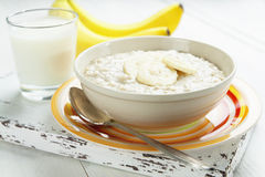 Oatmeal with bananas. Porridge with bananas in a yellow bowl and a glass of milk on the table Royalty Free Stock Photography