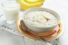 Oatmeal with bananas. Porridge with bananas in a yellow bowl and a glass of milk on the table Stock Photo