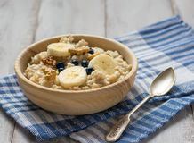 Oatmeal with bananas and spoon on the table stock images