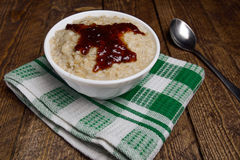 Oatmeal in a beautiful white bowl on the warm wooden background with jam.  Royalty Free Stock Photos