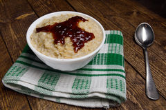 Oatmeal in a beautiful white bowl on the warm wooden background with jam.  Royalty Free Stock Photo