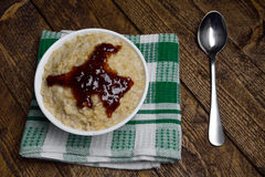 Oatmeal in a beautiful white bowl on the warm wooden background with jam.  Stock Photography
