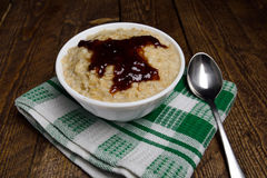 Oatmeal in a beautiful white bowl on the warm wooden background with jam.  Royalty Free Stock Image