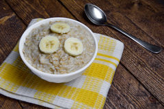 Oatmeal in a beautiful white bowl on a warm wooden background with slices of bananas.  Stock Photos