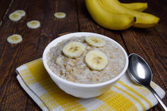 Oatmeal in a beautiful white bowl on a warm wooden background with slices of bananas.  Royalty Free Stock Photo