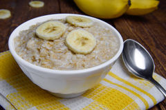 Oatmeal in a beautiful white bowl on a warm wooden background with slices of bananas.  Royalty Free Stock Photos