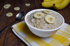 Oatmeal in a beautiful white bowl on a warm wooden background with slices of bananas.  Stock Images