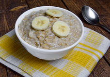 Oatmeal in a beautiful white bowl on a warm wooden background with slices of bananas.  Royalty Free Stock Photography