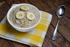 Oatmeal in a beautiful white bowl on a warm wooden background with slices of bananas.  Royalty Free Stock Image