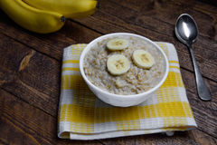Oatmeal in a beautiful white bowl on a warm wooden background with slices of bananas Stock Photo