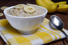 Oatmeal in a beautiful white bowl on a warm wooden background with slices of bananas.  Royalty Free Stock Images