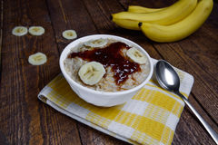 Oatmeal in a beautiful white bowl on a warm wooden background with slices of bananas  and jam. Oatmeal in a beautiful white bowl on a warm wooden background with Stock Photography