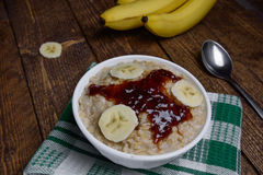 Oatmeal in a beautiful white bowl on a warm wooden background with slices of bananas  and jam. Oatmeal in a beautiful white bowl on a warm wooden background with Stock Image